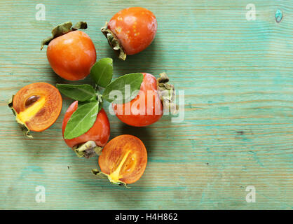 natural fresh organic fruit persimmon on a wooden table - Stock Photo