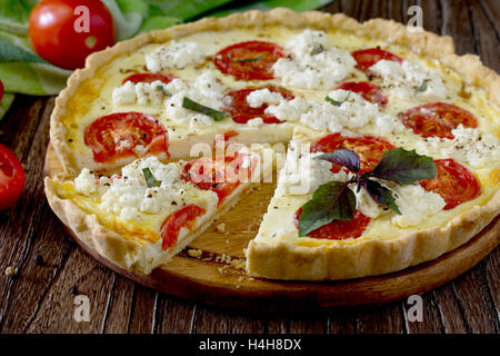 The classic quiche Lorraine pie with soft feta cheese, basil and tomatoes in a baking dish on a wooden background. - Stock Photo
