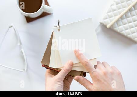 Female hands choosing a fabric pattern - Stock Photo