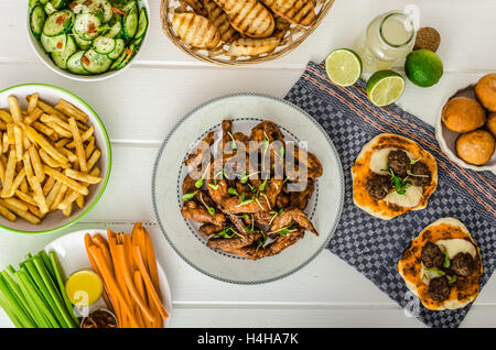 Chicken wings, vegetable, french fries, pizza, donuts, lime juice, dip, cucumber salad and toast. - Stock Photo