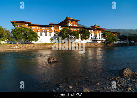 View over river to Punakha Dzong, a huge fortress monastery and administrative building in Bhutan - Stock Photo