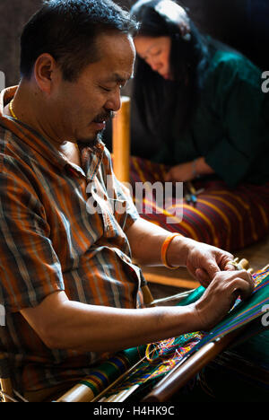 Man weaving traditional Bhutanese textiles on back-strap loom in Thimphu, Bhutan - Stock Photo