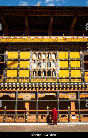 Buddhist monk standing beside the tall wooden galleries surrounding the monastery courtyard in Paro Dzong, Bhutan - Stock Photo