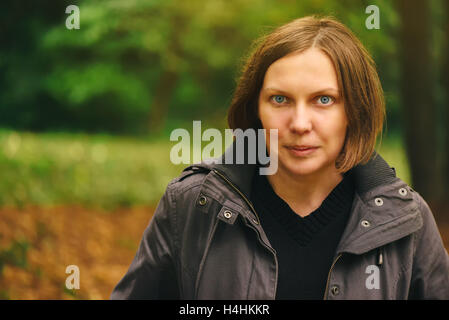 Portrait of beautiful young adult friendly woman posing in autumn park and looking at camera - Stock Photo