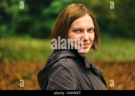 Beautiful smiling young adult friendly woman posing in autumn park and looking at camera - Stock Photo