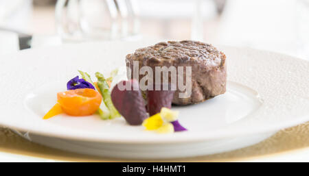 minimalistic dish steak with vegetables on a white plate - Stock Photo