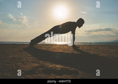 Man practicing yoga in various poses (asana) by the sea - Stock Photo