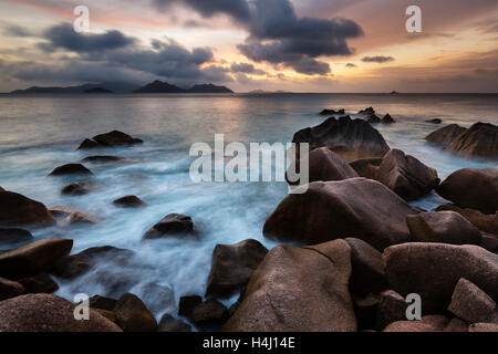 Sunset long exposure with view to Praslin from La Digue, Seychelles with granite rocks in the foreground - Stock Photo