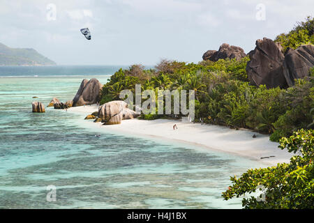 High angle view of the famous Anse Source D'Argent in La Digue, Seychelles with a kite surfer and some early tourists - Stock Photo