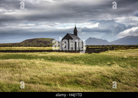 Scenery of black wooden church of Budir in Iceland with the pasture and mountains in the background - Stock Photo