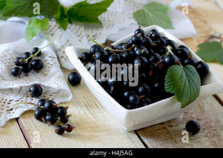 Ripe berries of a black currant in a bowl on a wooden table, selective focus. - Stock Photo