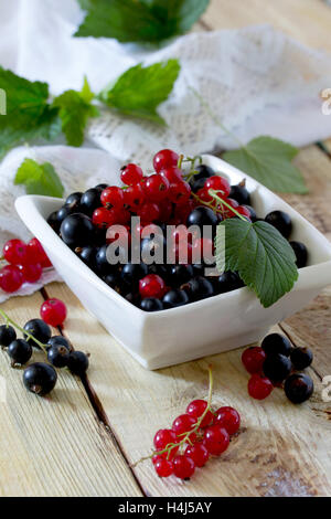 Ripe berries are black and red currants in a bowl on a wooden table, selective focus. - Stock Photo