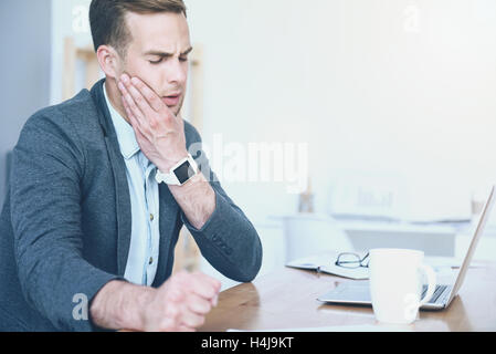 Good looking young man working and having toothache. - Stock Photo
