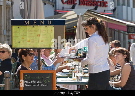 Waitress serving customers in outdoor cafe in Beaune centre, Burgundy, Cote d'Or, France - Stock Photo