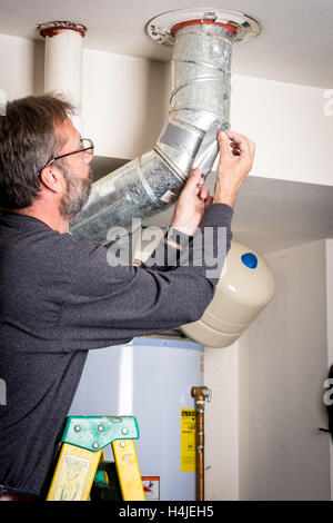 Adding tape to home duct work standing on a ladder - Stock Photo