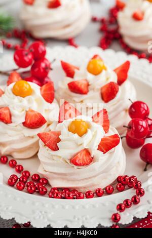 Pavlova meringue cake decorated with fresh strawberry and cape gooseberry on festive background - Stock Photo