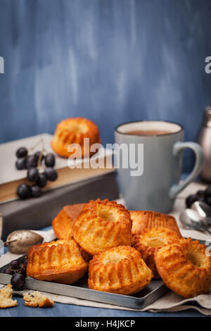 Fresh homemade delicious mini bundt cakes (muffins) and cup of coffee on background - Stock Photo