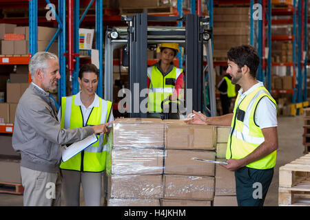 Warehouse manager and workers preparing a shipment - Stock Photo