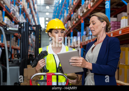 Warehouse manager with interacting female worker over digital tablet - Stock Photo