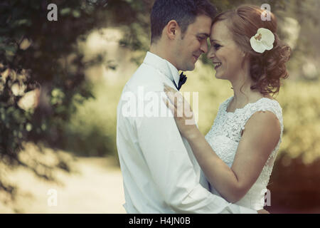 Beautiful bride and groom kissing outdoors after ceremony - Stock Photo