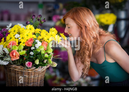 Female florist smelling flower - Stock Photo