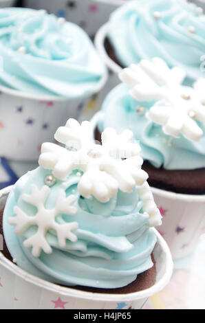 cup cakes with snowflakes decorating in the color of light blue for a celebrating birthday party - Stock Photo