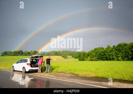 Photographers photographing double rainbow over fields during storm. Upper Bavaria. Germany. - Stock Photo