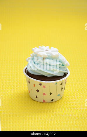 single cup cake with snowflakes decorating in the color of light blue for a birthday party, with yellow background - Stock Photo