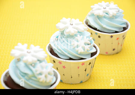 cup cakes with snowflakes decorating in the color of light blue for a birthday party, with yellow background - Stock Photo