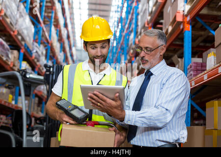 Warehouse manager with interacting male worker over digital tablet - Stock Photo
