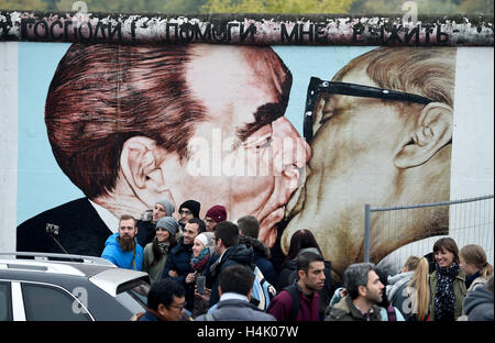 Tourists are photographed at the shortly-to-open fence in front of the painting 'My God, Help Me to Survive This - Stock Photo