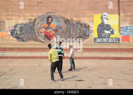 Three indian boys playing in front of a graffiti wall on the ghats of Varanasi, Uttar Pradesh, India - Stock Photo