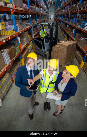 Warehouse manager interacting with client and female worker - Stock Photo