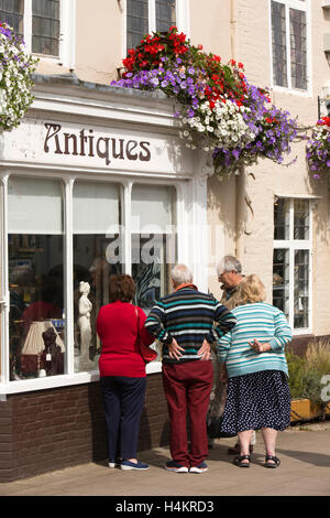 England, Berkshire, Hungerford, High Street, senior shoppers looking in window of Hungerford Arcade antiques centre - Stock Photo