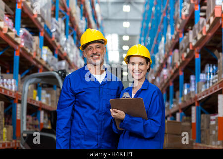 Warehouse workers standing together in warehouse - Stock Photo