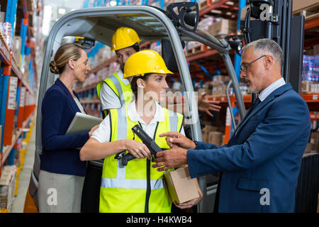 Warehouse manager and client interacting with co-workers - Stock Photo