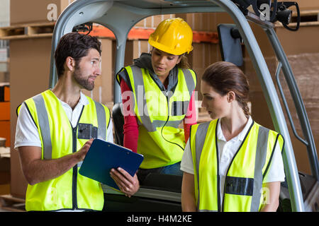 Warehouse workers talking with forklift driver - Stock Photo