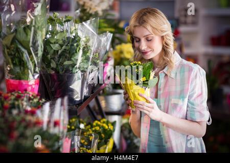 Happy female florist smelling a flower bouquet - Stock Photo