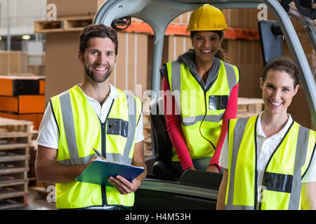 Portrait of warehouse workers and forklift driver - Stock Photo