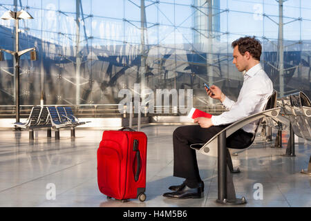 Businessman traveling with smartphone and luggage - Stock Photo