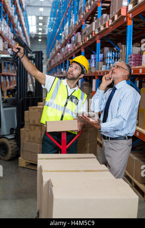 Warehouse manager interacting with male worker - Stock Photo