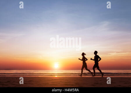 Silhouette of two sportive runners running on the beach at sunset, concept about healthy lifestyle and wellbeing - Stock Photo