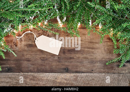 Christmas tree pine branches, blank card and decorative lights over a rustic background of barn wood. Image shot - Stock Photo
