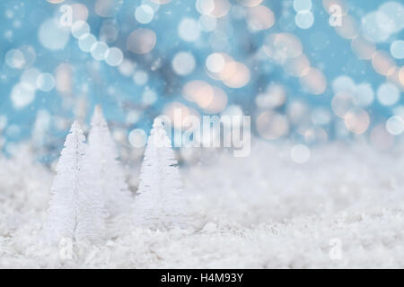 Miniature white Christmas trees against snowy bokeh background with lights. Macro with extreme shallow depth of - Stock Photo