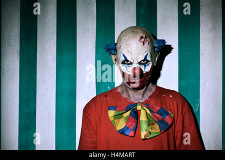 closeup of a scary evil clown wearing a dirty costume, with the circus tent in the background - Stock Photo