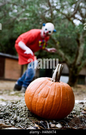 closeup of a pumpkin outdoors and a scary evil clown in the background - Stock Photo