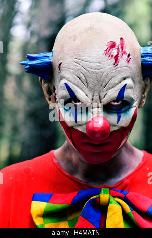 closeup of a scary evil clown staring at the observer, in the woods - Stock Photo
