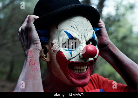 closeup of a scary evil clown in the woods smiling while is adjusting his bowler hat - Stock Photo