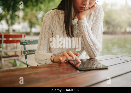 Young woman using digital tablet at outdoor cafe. Female browsing website pages on touch pad while in coffee shop. - Stock Photo