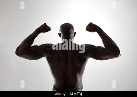 Strong back of a black muscular man flexing his arms against grey background. Rear view of african fitness model - Stock Photo